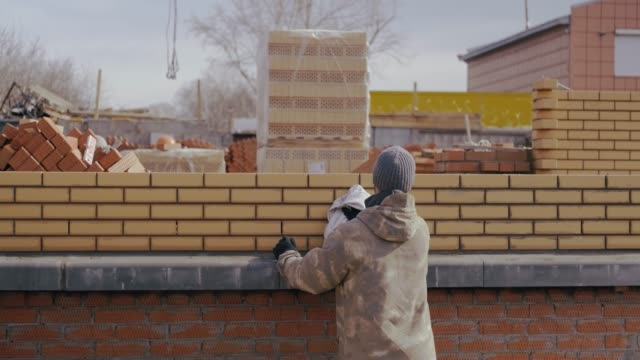 Professional builder in khaki uniform wipes brick wall after his work. Worker overwrites brick wall. Builder wipes excess solution between seams. Builder is building house. Construction of building. Professional builder wipes brick wall after his work. Worker builds house. Build russian ethnicity stock videos & royalty-free footage