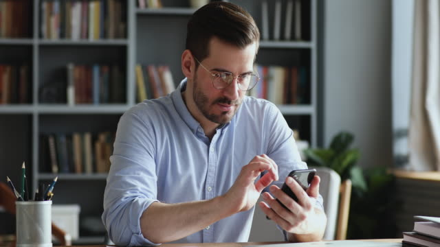 Professional businessman using modern smartphone texting message in office