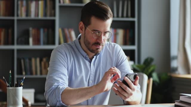 vidéos et rushes de homme d'affaires professionnel utilisant le message moderne de texto de smartphone dans le bureau - message sms