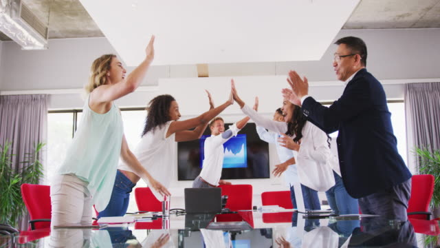 vídeos de stock e filmes b-roll de professional businesspeople clapping and giving high five to each other in meeting room - trabalho de design