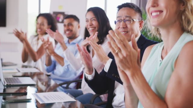 vídeos de stock e filmes b-roll de professional businesspeople clapping together in meeting room in modern office in slow motion - trabalho de design