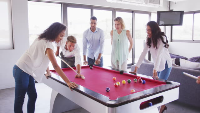 Professional businesspeople playing billiards in modern office in slow motion