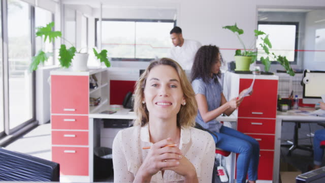 vídeos de stock e filmes b-roll de professional businesswoman smiling while sitting on her desk in modern office in slow motion - trabalho de design