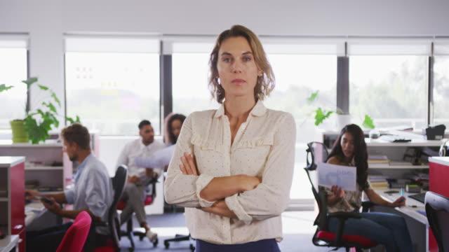 vídeos de stock e filmes b-roll de professional businesswoman standing with her hands folded in modern office in slow motion - trabalho de design