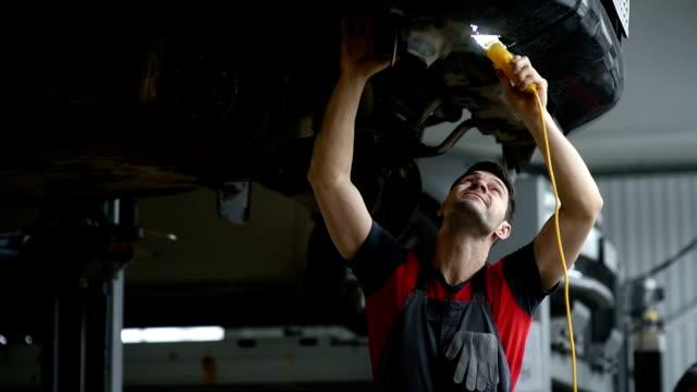 en professionell bilmekaniker arbetar i en verkstad, kontrollerar han bilen upp på hissen - mekaniker bildbanksvideor och videomaterial från bakom kulisserna