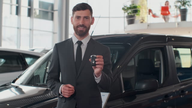 Professional car salesman smiling happily holding car keys standing in front of new cars at the dealership. Professional car salesman smiling happily holding car keys standing in front of new cars at the dealership car salesperson stock videos & royalty-free footage