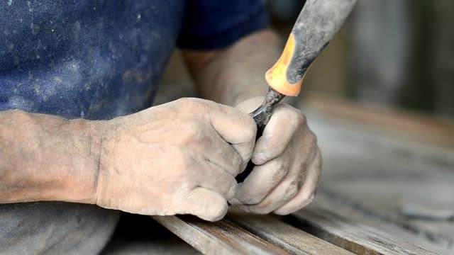 Professional carpenter at work, he is carving wood using a woodworking tool, hands close up, carpentry and craftsmanship concept Professional carpenter at work, he is carving wood using a woodworking tool, carpentry and craftsmanship concept carpenter stock videos & royalty-free footage