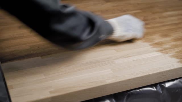 professionell snickare tillämpa ett lager av en olja på den slipade träbit - construction workwear floor bildbanksvideor och videomaterial från bakom kulisserna