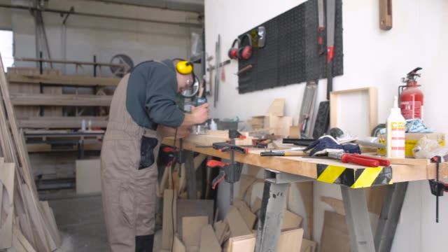 Professional carpenter polishing wood with hand grinder