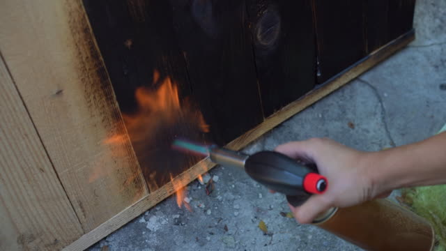 Professional carpenter using old traditional japanese technique. Burning wood planks with gas burner