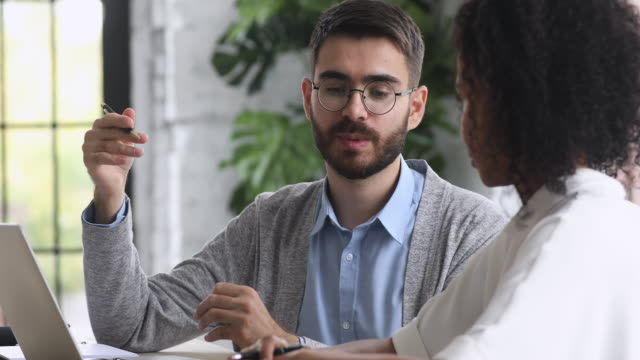 Professional caucasian mentor helping african intern with corporate software Professional caucasian male mentor teacher helping african female intern with corporate software teach trainee training colleague consulting client using laptop working together in office, internship coach stock videos & royalty-free footage