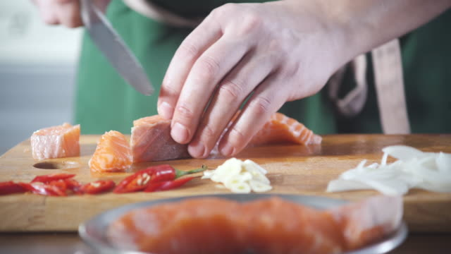 professionell skär färsk lax innan att laga mat på köksrestaurang. sushikocken skivor fisk. livsmedelsingrediensen. matlagning på köket. tillagad för gourmet. laga mat att äta. gastronomi kulinariska. - tallrik uppätet bildbanksvideor och videomaterial från bakom kulisserna