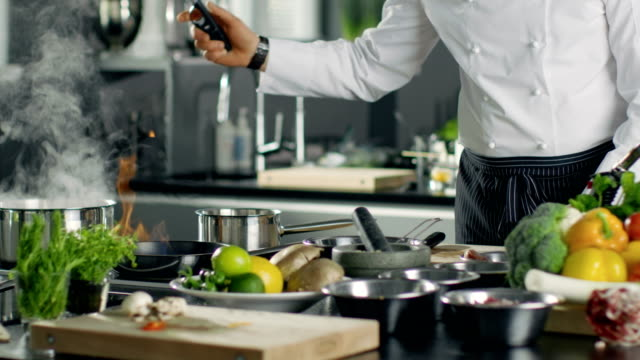 Professional Chef Fires up Oil on a Pan. Flambe Style Cooking. He Works in a Modern Kitchen with Lots of Ingredients Lying Around. video