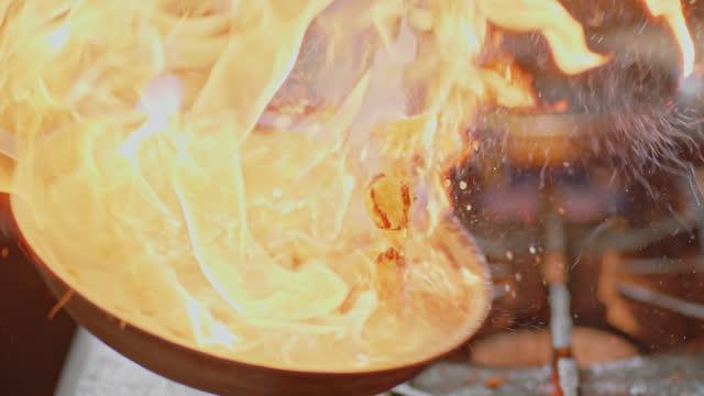 slo mo.プロフェッショナルシェフは、ダイナーの商業キッチンで炎のストーブの上にフライパンでバナナをフライドポテト。 - 料理人点の映像素材/bロール