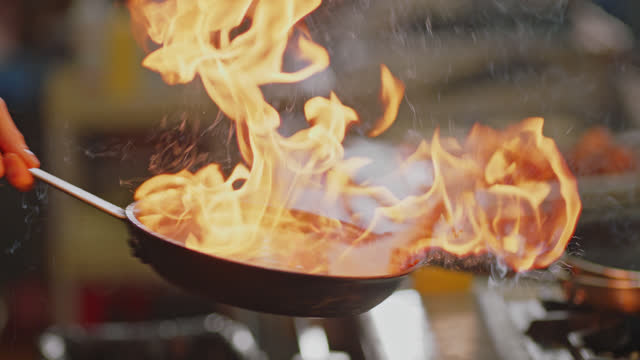 SLO MO. Professional chef fries bananas in a pan over a flaming stove in a commercial kitchen at a diner.  spice stock videos & royalty-free footage