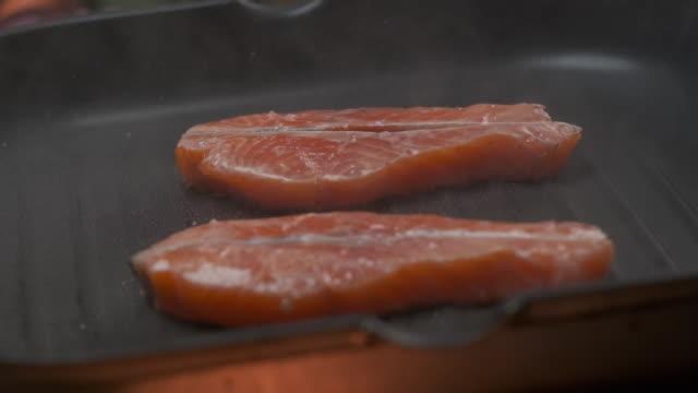 vidéos et rushes de le chef professionnel grille le steak de filet de poisson rouge. ralenti - recette