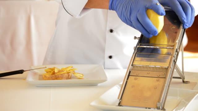 Professional chef hands cutting potatoes with knife and mandolin video
