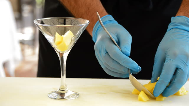 Professional chef hands throwing dice mango fruit in cocktail glass video