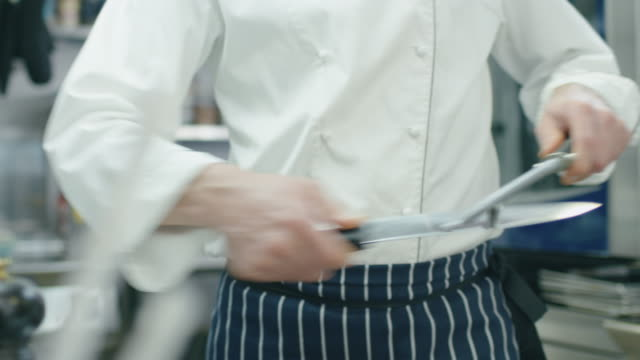 Professional chef in a commercial kitchen in a restaurant or hotel is sharpening knifes. video