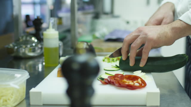 Professional chef in a commercial kitchen in a restaurant or hotel is slicing green vegetables. video