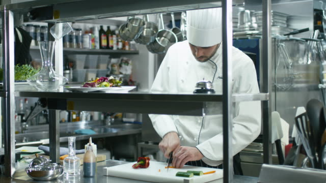 Professional chef in a commercial kitchen is slicing green vegetables. video