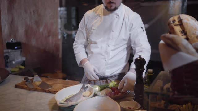 A professional chef in a white jacket and rubber chef gloves prepares a delicious dish