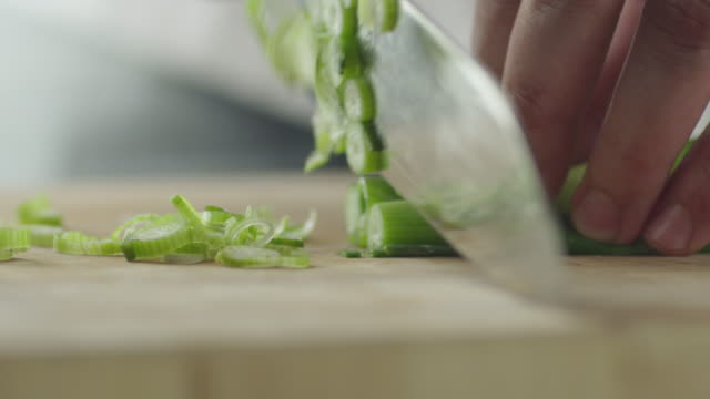 Professional Chef is Rapidly Chopping Spring Onion. Close-up. Professional Chef is Rapidly Chopping Spring Onion. Close-up. Shot on RED Cinema Camera in 4K (UHD). cutting stock videos & royalty-free footage