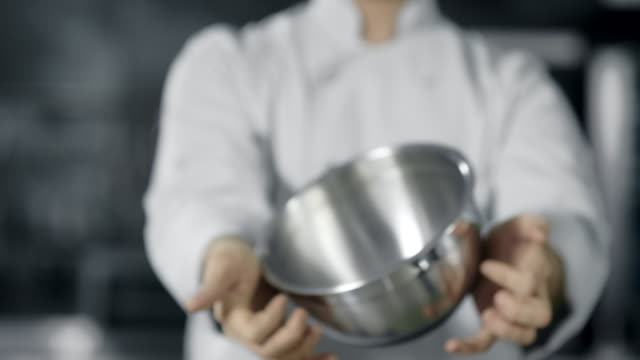 Professional chef playing with kitchen tools. Close up chef hands rolling bowl