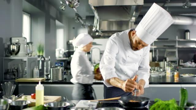 profesyonel chef sıkar limon suyu ile kırmızı balık fileto üzerine sıcak tava üzerine. o bir modern mutfakta çalışıyor. - chef stok videoları ve detay görüntü çekimi