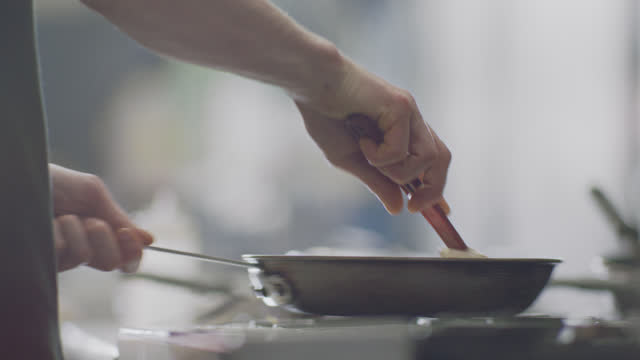 vídeos de stock e filmes b-roll de professional chef stirs eggs in a pan while cooking in a commercial kitchen at a diner. - cozido