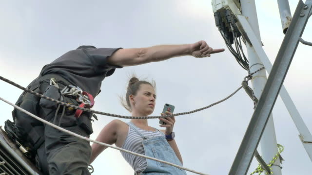 Professional climber with woman near the network tower at the roof video