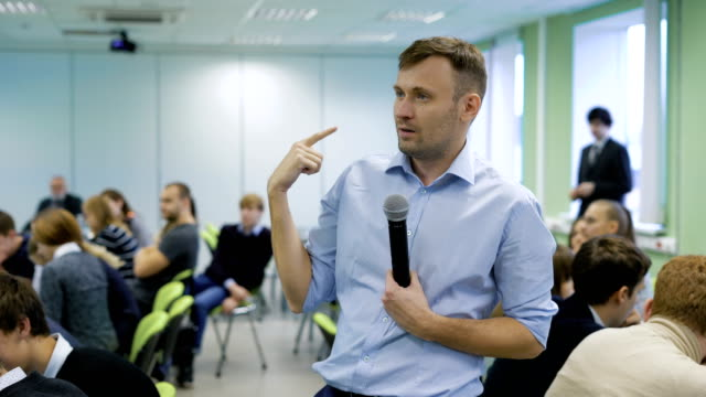 Professional coach in blue shirt speaking into the microphone and gesticulating at workshop for future top managers of a business company. Audience sitting at the conference room at the table video