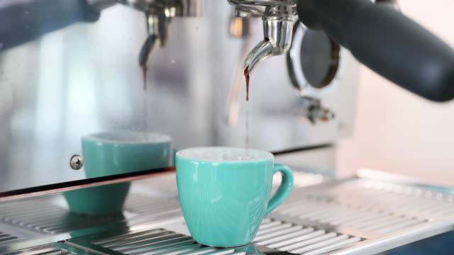 professional coffee machine making espresso in a green mint cup. - espresso filmów i materiałów b-roll