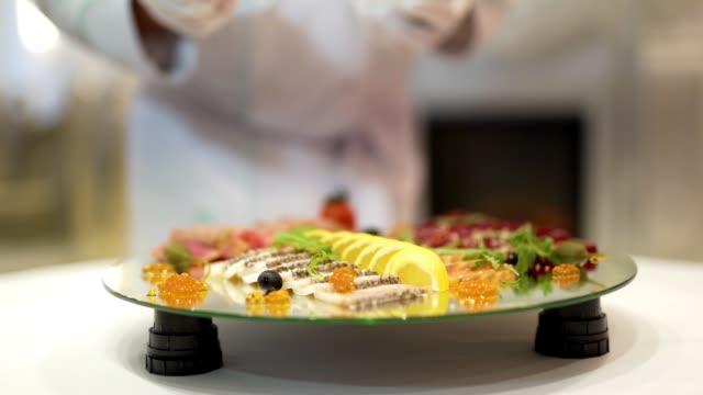 vidéos et rushes de le cuisinier professionnel met le caviar par une cuillère sur la plaque avec des fruits et des collations de viande. - banquet