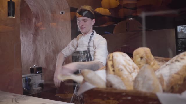 Professional cook spinning and throwing pizza dough up in kitchen of restourant.