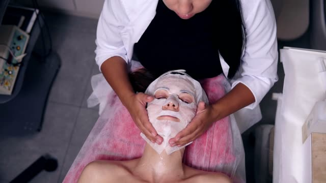Professional cosmetologist holding her hands on woman's face while apllying special mask on female client's face and neck. Professional carboxytherapy for young woman in spa salon