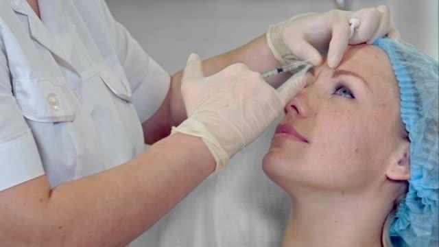 Cosmetóloga profesional haciendo inyecciones de belleza a su revitalización mujer cliente anti envejecimiento concepto profesional botox belleza rellenos hialurónico - vídeo
