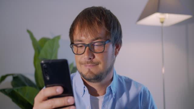 Professionele Creatieve Mens in eyeglasess Zitting in De Studio van het Bureau van het Huis met Smartphone video