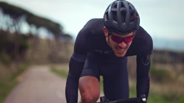 vídeos y material grabado en eventos de stock de ciclista profesional que lucha por andar en bicicleta durante el entrenamiento - luchar