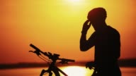 istock Professional cyclist takes off his protective glasses while standing at a beautiful sunset. 1179961366