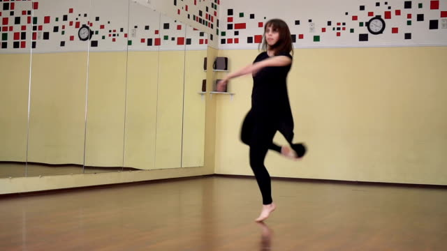 eine professionelle tänzerin mädchen in eine schwarze kleidung tanzt in eine große trainingshalle - gymnastikanzug stock-videos und b-roll-filmmaterial