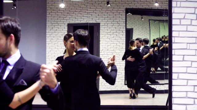 Professional dancers dancing tango in ballroom. Portrait of professional dancing couple in black suits dancing tango in the ballroom. Two mirrors opposite each other create a lot of reflections dance studio stock videos & royalty-free footage