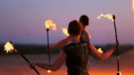 istock Professional dancers women make a fire show and pyrotechnic performance at the festival with burning sparkling torches. 1158419514
