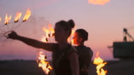 istock Professional dancers women make a fire show and pyrotechnic performance at the festival with burning sparkling torches. 1158425199