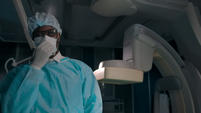 Professional dark-skinned surgeon removes the mask after surgery and shows his hands in gloves