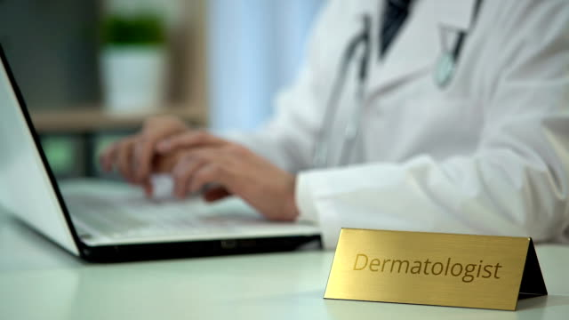 Professional dermatologist chatting with patient on laptop, online consultation video