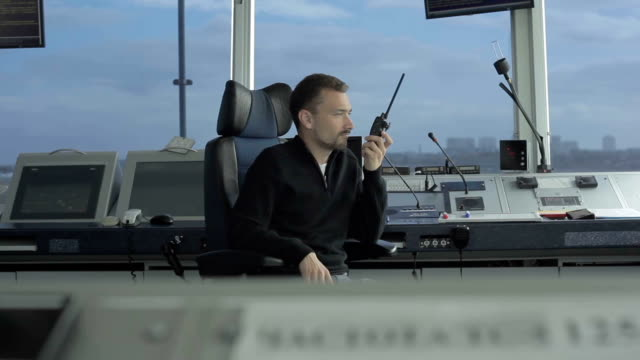 Professional dispatcher speaks with portable radio in control tower in airport video