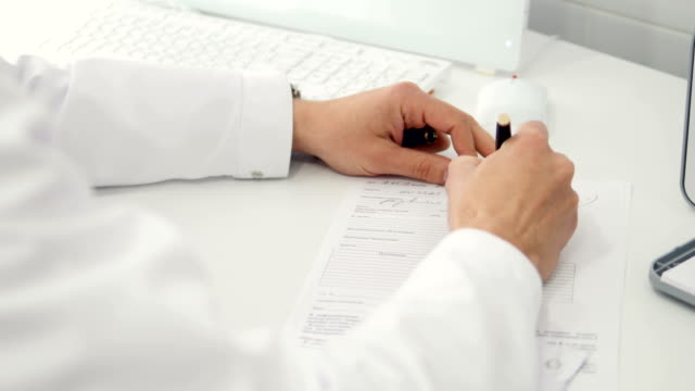 Professional doctor writes recipe, doing paperwork in clinic. Health care and insurance concept. 4K.