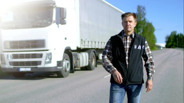 Profesional Driver sale de blanco estacionado Semi camión con remolque de carga conectado. El controlador se encuentra en medio del camino y orgullosamente cruza los brazos. - vídeo