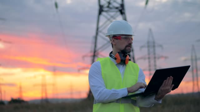 Professional electrician, engineer working at the power line with laptop. Power Lines and Engineer sunset background. Electrical engineer observing high-voltage equipment. 4K. high voltage sign stock videos & royalty-free footage